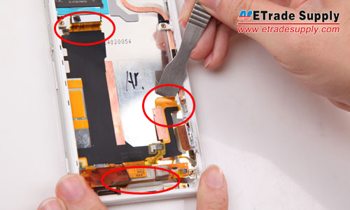 Pry up the three connectors to release the motherboard flex cable ribbon